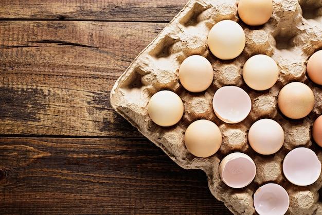Bovenaanzicht close-up van eierschaal en hele eieren in kartonnen gerecycleerde eierdoos met kopie ruimte op houten