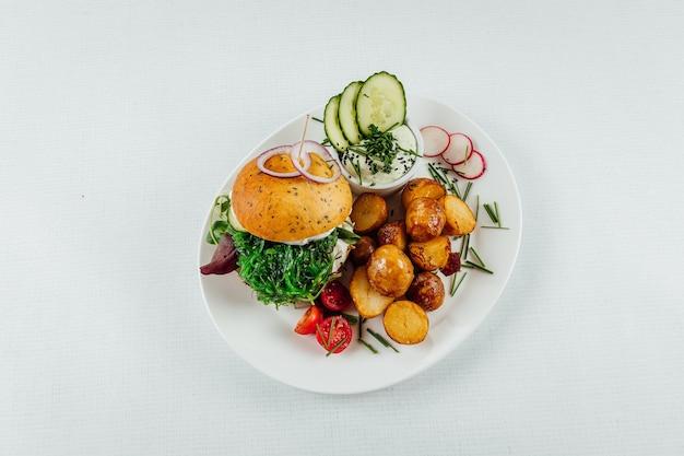Bovenaanzicht close-up van geroosterde aardappelen met tomaat en radijs naast een hamburger met rucola