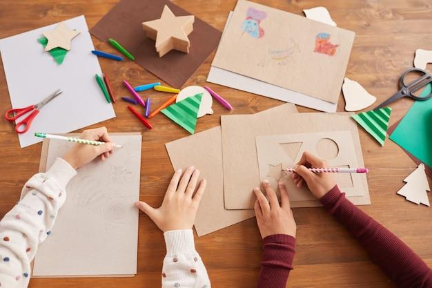 Bovenaanzicht close-up van kinderen tekenen van afbeeldingen tijdens kunst- en ambachtles op school, kopie ruimte