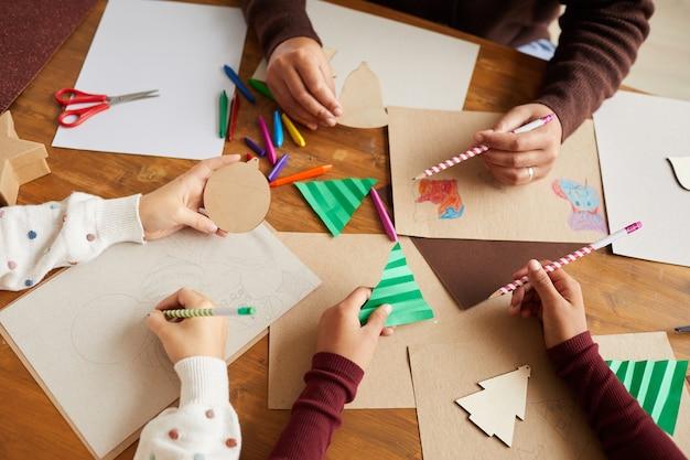 Bovenaanzicht close-up van kinderen tekenen van afbeeldingen tijdens kunst- en ambachtles op school, kopieer ruimte