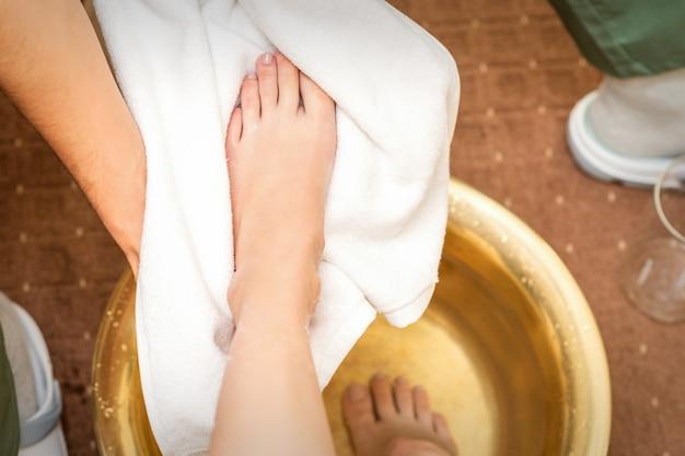 Bovenaanzicht close-up van mannelijke therapeut drogen been van een blanke vrouw met een handdoek na het wassen in een spa schoonheidssalon