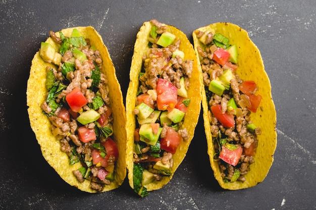 Bovenaanzicht, close-up van mexicaanse taco's met vlees, avocado, tomatensalsa, kruiden in gele maïstortilla op zwarte rustieke stenen achtergrond.