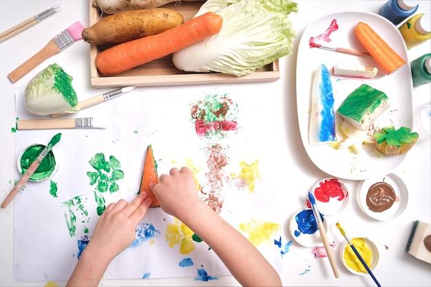 Bovenaanzicht close-up van peuter jongen kind handen, kind maken van illustraties van plantaardige stempelen thuis