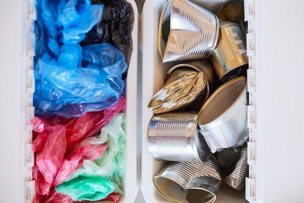 Bovenaanzicht close-up van plastic zakken en metalen blikjes opgeslagen op materiaalsoort en klaar voor recycling, afval sorteren concept