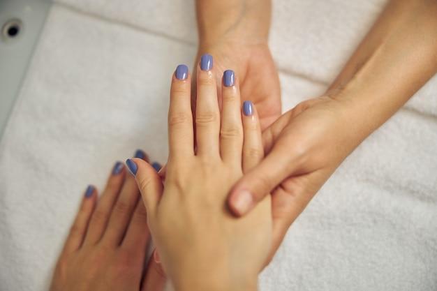 Bovenaanzicht close-up van schoonheidsspecialiste die vrouwelijke handen vasthoudt na het doen van manicure met gel polish