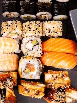 Bovenaanzicht close-up van sushi rollen in verscheidenheid op zwarte stenen achtergrond