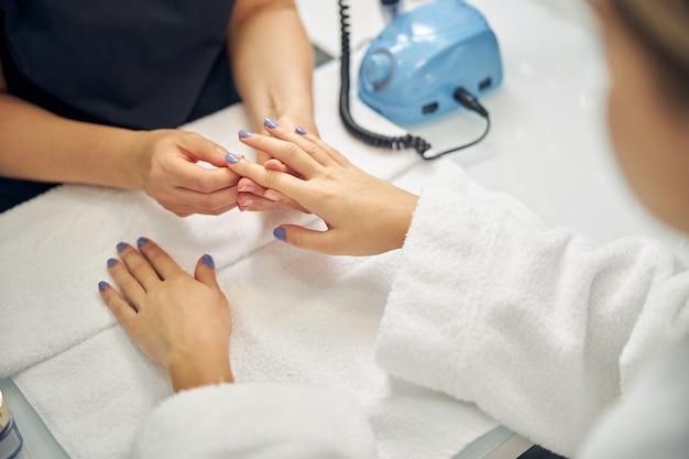 Bovenaanzicht close-up van vrouwelijke handen bedekt met blauwe gellak door professional in spa salon