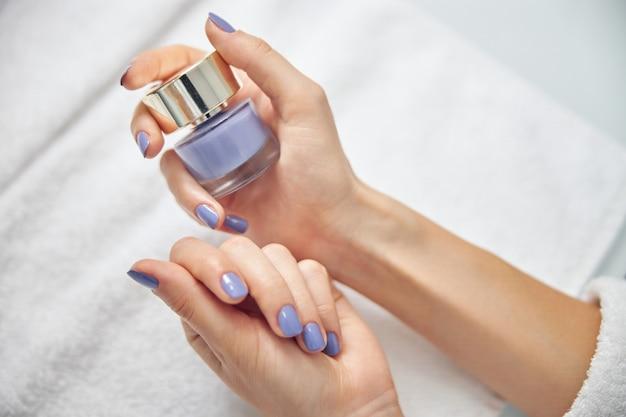 Bovenaanzicht close-up van vrouwelijke handen met heldere manicure met gellak boven handdoek