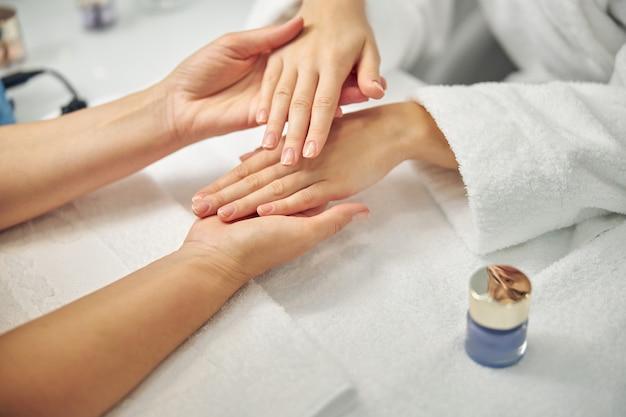 Bovenaanzicht close-up van vrouwelijke handen met naaktlak terwijl nagelstyliste ze vasthoudt na schoonheidsprocedure
