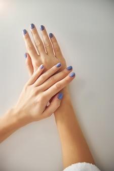 Bovenaanzicht close-up van vrouwelijke handen met nagels bedekt met blauwe nagellak geïsoleerd op een witte achtergrond