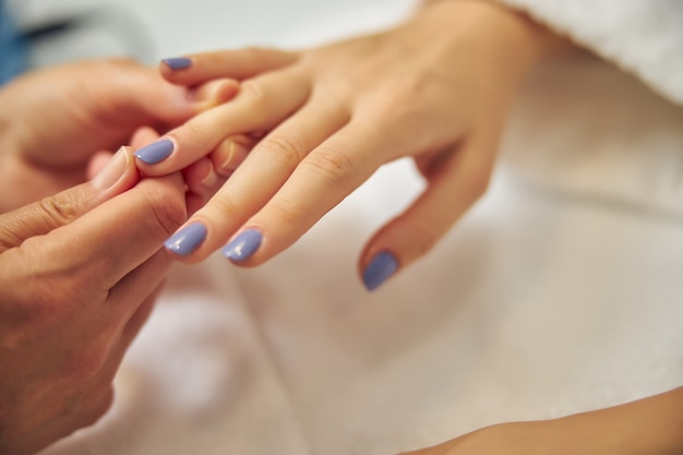Bovenaanzicht close-up van vrouwelijke vingers bedekt met blauwe gellak door professional in salon