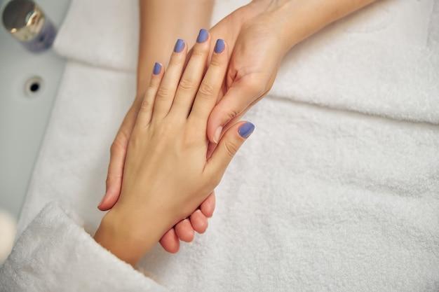 Bovenaanzicht close-up van vrouwelijke vingers met nagels gekleurd in blauw pools terwijl de meester ernaar kijkt