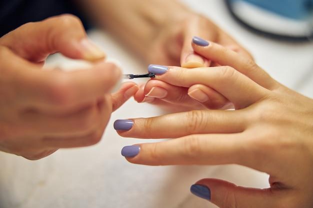 Bovenaanzicht close-up van vrouwelijke vingers terwijl artiest nagels bedekt met kleurgellak