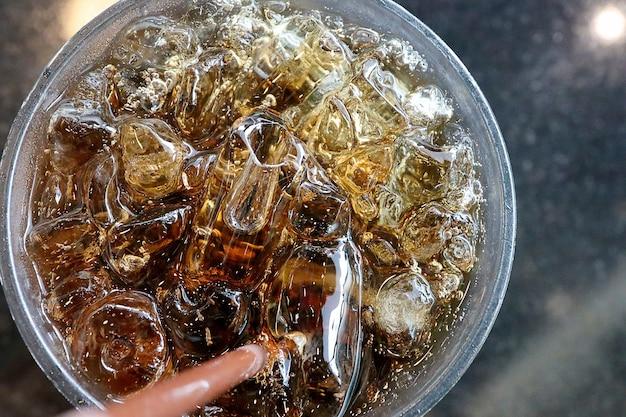 Bovenaanzicht cola in het glas met ijsblokjes.