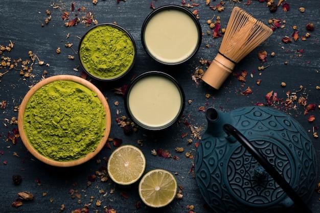 Bovenaanzicht collectie groene thee poeder naast theepot