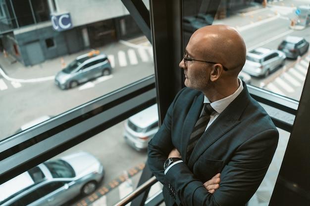 Bovenaanzicht. contemplatieve kale zakenman in pak en bril wegkijken in het raam of