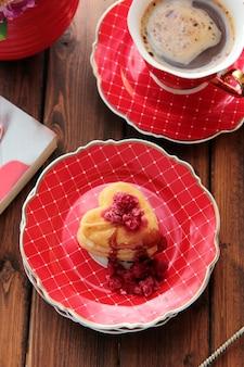 Bovenaanzicht cookies in de vorm van een hart met frambozen met een kopje koffie