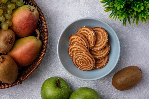 Bovenaanzicht cookies in een kom met kiwi peer en groene appels op een witte achtergrond