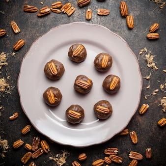 Bovenaanzicht cookies in plaat met noten op zwarte achtergrond.