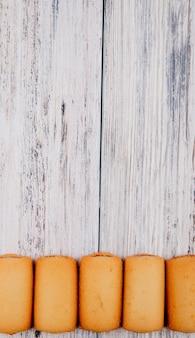 Bovenaanzicht cookies met jam aan de onderkant met kopie ruimte op witte houten achtergrond