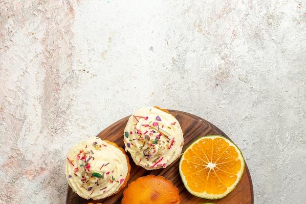 Bovenaanzicht cookies smakelijke koekjes en gesneden sinaasappel op de houten snijplank op tafel