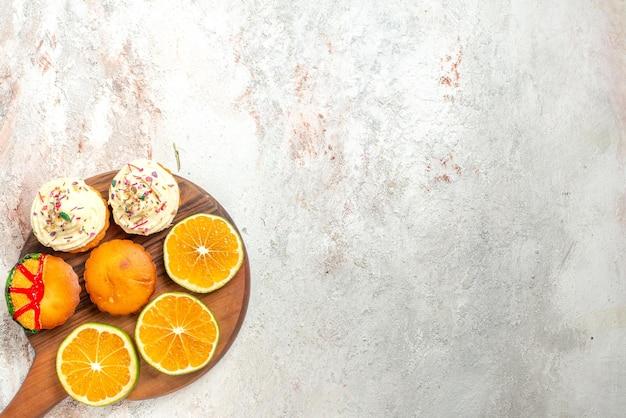 Bovenaanzicht cookies smakelijke koekjes en gesneden sinaasappel op de snijplank aan de linkerkant van de tafel