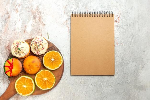Bovenaanzicht cookies smakelijke koekjes en gesneden sinaasappel op de snijplank naast het crèmekleurige notitieboekje op tafel