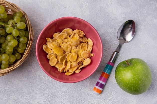 Bovenaanzicht cornflakes in een kom met een theelepel met een groene appel en groene druiven op een witte achtergrond