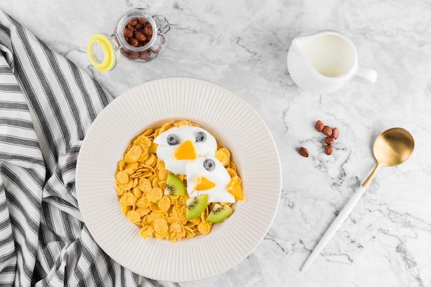 Bovenaanzicht cornflakes met fruit en yougurt