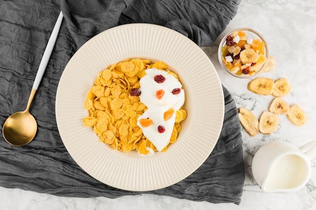 Bovenaanzicht cornflakes met yoghurt en gedroogde vruchten