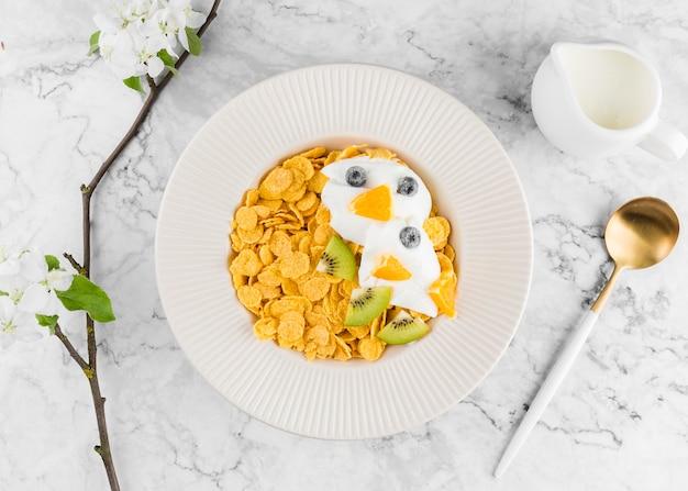 Bovenaanzicht cornflakes met yougurt en fruit