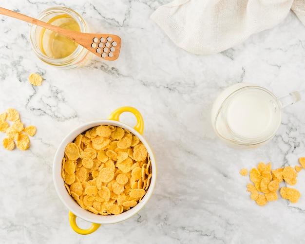 Bovenaanzicht cornflakes met yougurt en honing