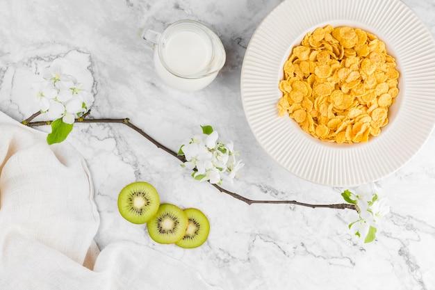 Bovenaanzicht cornflakes met yougurt en kiwi