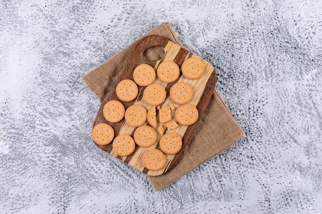 Bovenaanzicht crackers op linnen tas en houten plank witte steen horizontaal