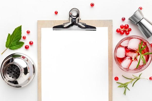 Bovenaanzicht cranberry wodka glas met leeg klembord