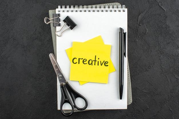 Bovenaanzicht creatief geschreven op gele notitie schaar zwarte pen bindmiddel clips op notebook op donkere achtergrond