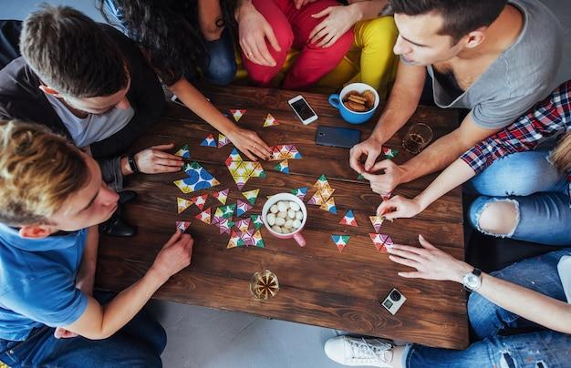 Bovenaanzicht creatieve foto van vrienden zitten aan houten tafel. plezier tijdens het spelen van bordspel