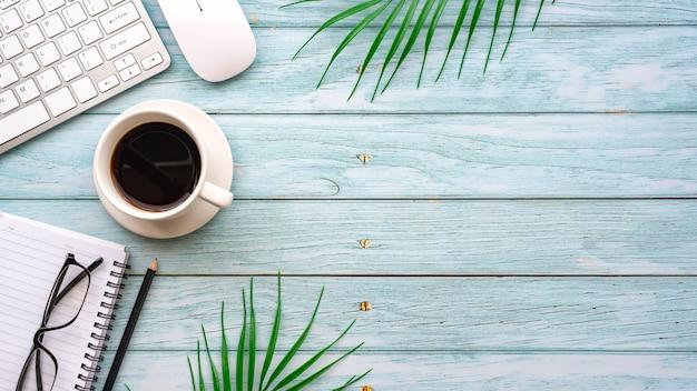 Bovenaanzicht creatieve werkruimte met laptops toetsenborden koffieglazen geplaatst op de houten tafel.