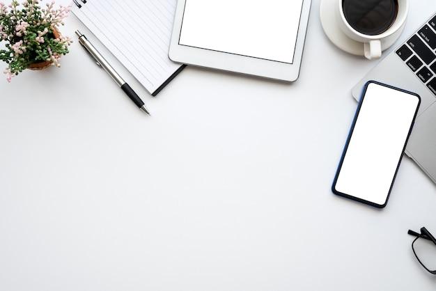 Bovenaanzicht creatieve werkruimte, smartphone bril toetsenbord witte tafel kopieerruimte.