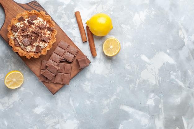 Bovenaanzicht crème kleine cake met chocoladerepen citroenen op het licht bureau zoete cake suiker crème chocolade