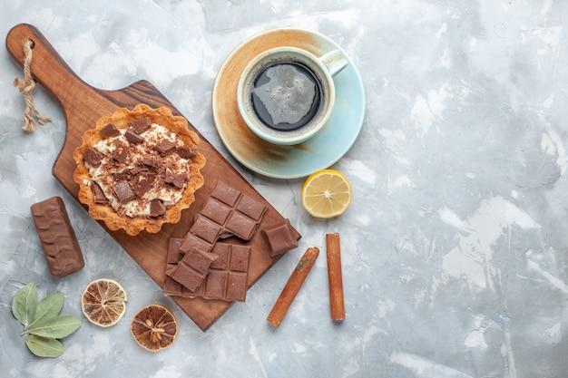Bovenaanzicht crème kleine cake met chocoladerepen en thee op licht bureau zoete cake crème chocolade