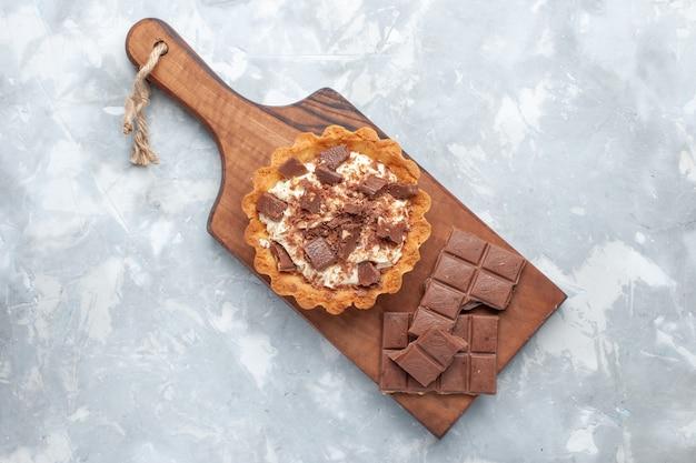 Bovenaanzicht crème kleine cake met chocoladerepen op de witte achtergrond zoete cake suiker crème chocolade