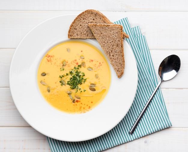 Bovenaanzicht creme soep met sneetjes brood