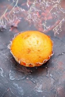 Bovenaanzicht cupcake een smakelijke cupcake op tafel naast de boomtakken