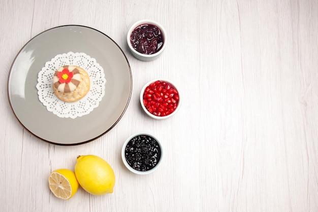 Bovenaanzicht cupcake en jam bord van smakelijke cupcake op het kanten kleedje naast de kommen met zaden van granaatappeljam en citroen op tafel