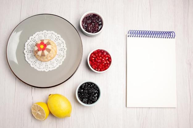 Bovenaanzicht cupcake en jamplaat van smakelijke cupcake op het kanten kleedje naast de witte notebookkommen met zaden van granaatappeljam en citroen op tafel