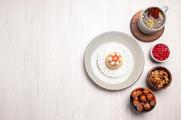 Bovenaanzicht cupcake en thee bord van smakelijke cupcakes naast het kopje thee kommen van granaatappel en hazelnoten op tafel