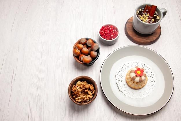 Bovenaanzicht cupcake en thee bord van smakelijke cupcakes naast het kopje thee zaden van granaatappel en noten in de bwron kommen op tafel
