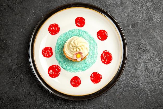 Bovenaanzicht cupcake smakelijke cupcake met rode saus op de witte plaat in het midden van de zwarte tafel