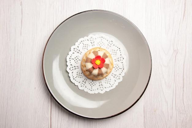 Bovenaanzicht cupcake smakelijke cupcake op het kanten kleedje op de grijze plaat op de witte tafel